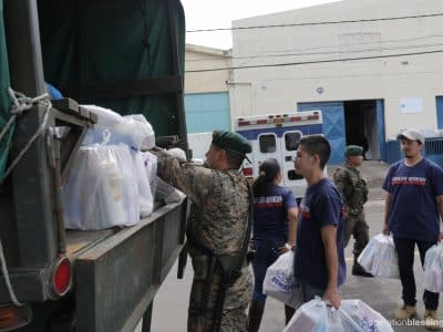 : OBI staff help soldiers from the Guatemalan Army load emergency aid kits onto a truck.