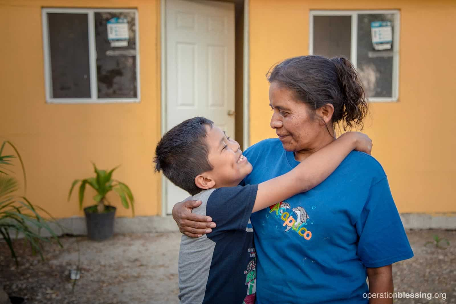 Uziel hugs his mother in front of their new home.