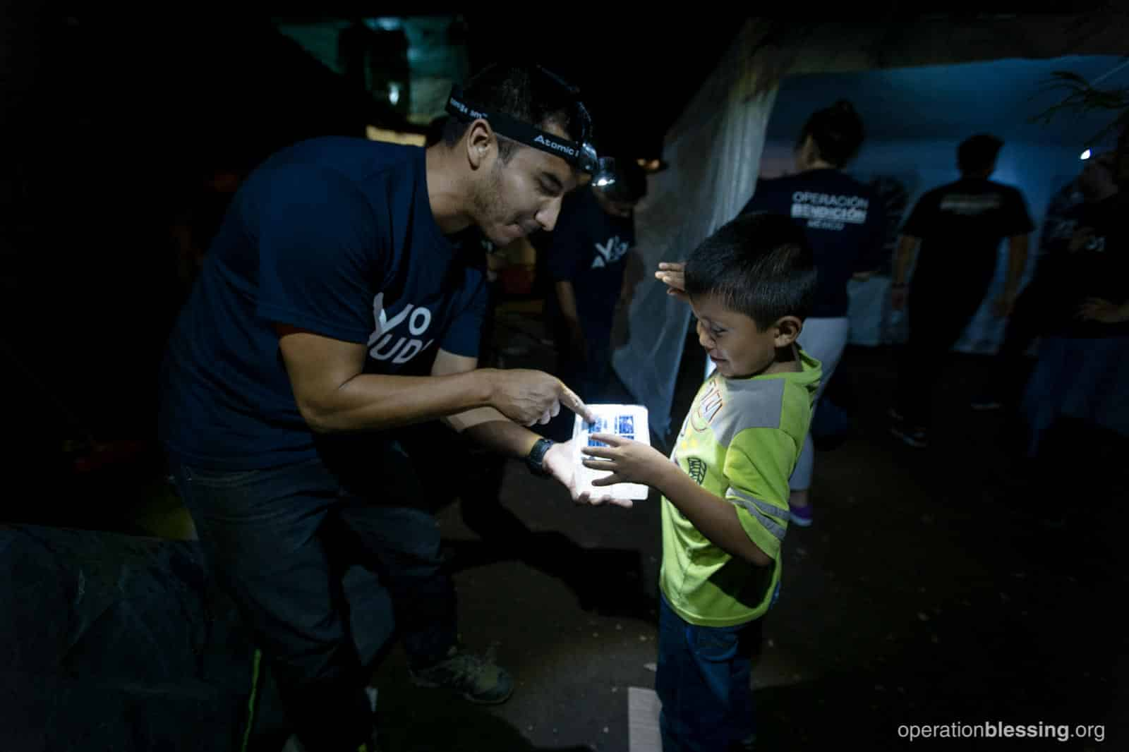 An OB Mexico team member presents Uziel with a solar lantern.