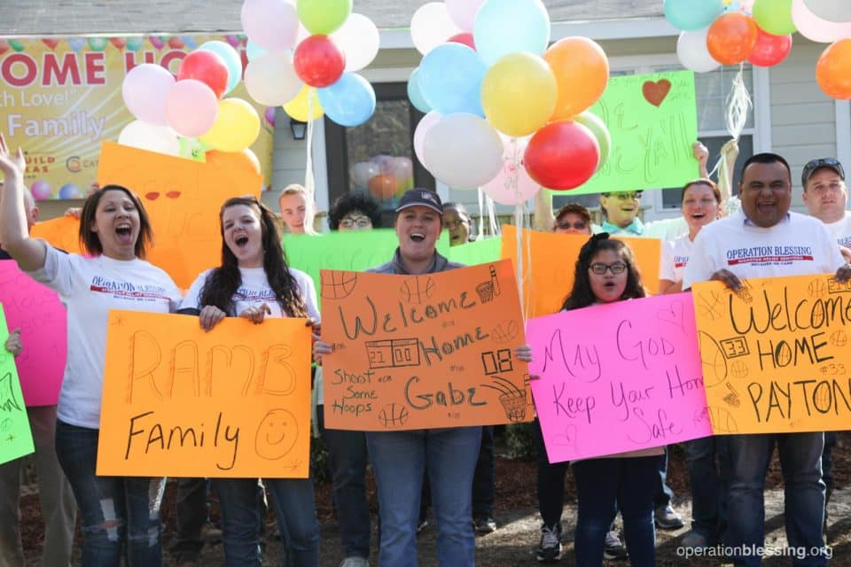 Operation Blessing workers meet the family with sign and balloons.