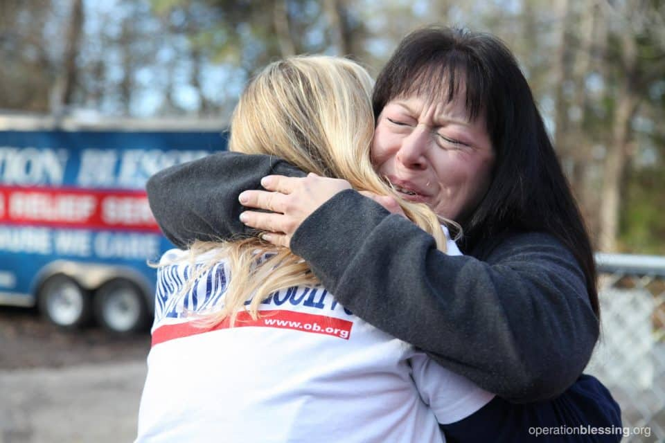 Peggy gives a hug to an Operation Blessing volunteer.