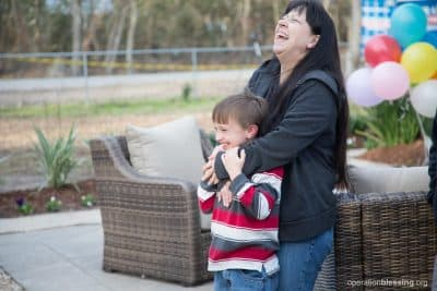 Gabe and his mom, Peggy, laugh outside their restored home.