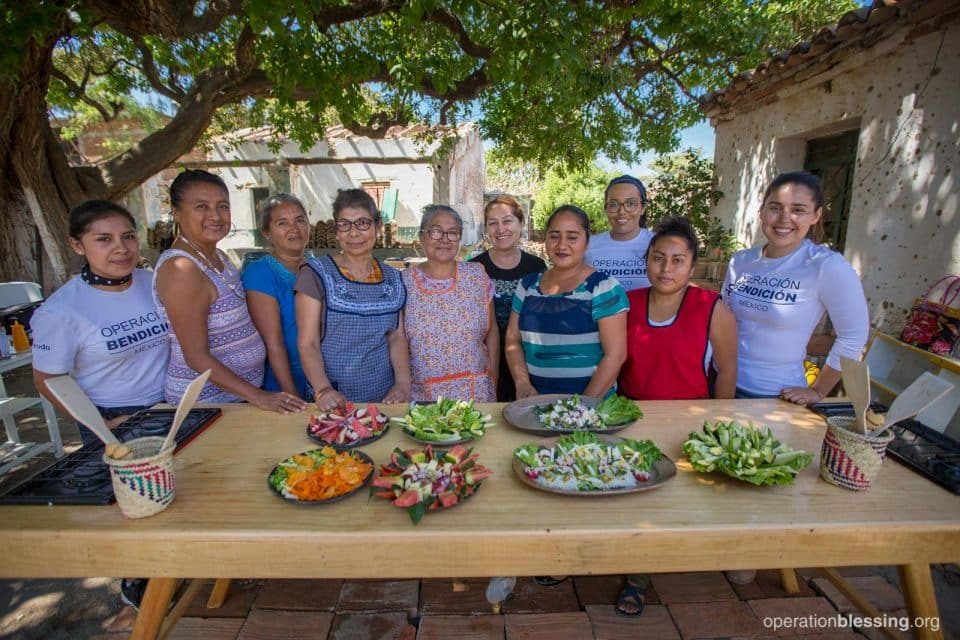 The nutrition class stands with their beautiful table covered with salads.