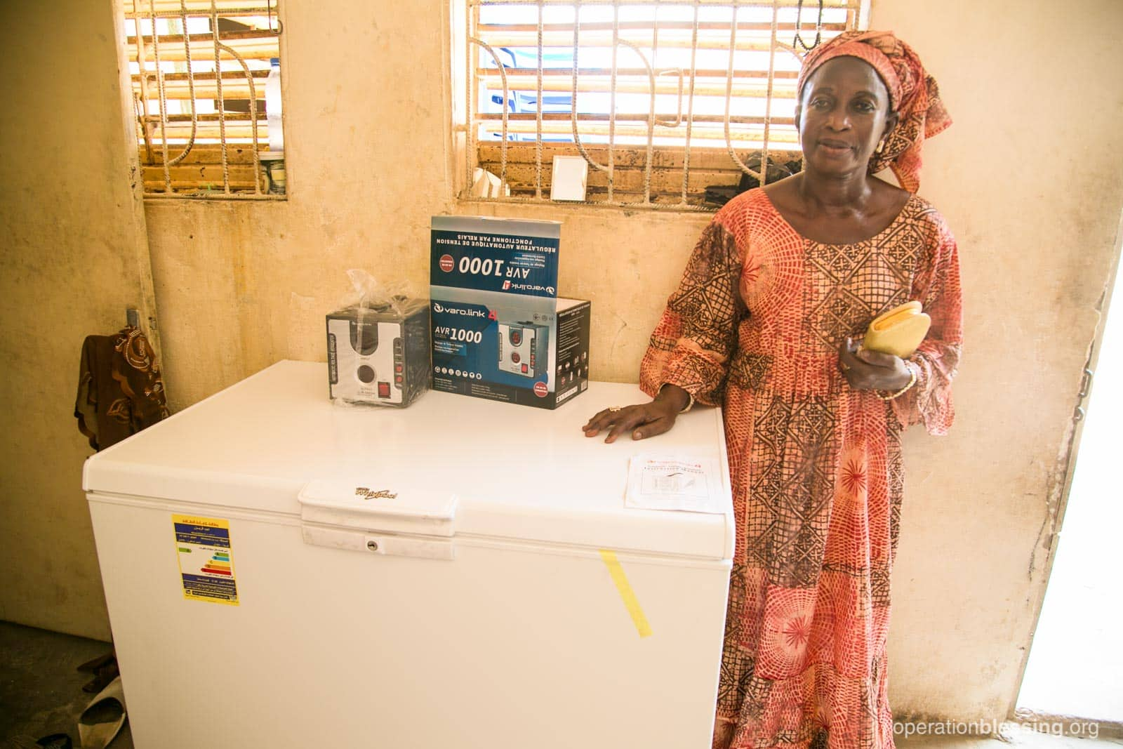 Seynabou stands beside her new refrigerator from Operation Blessing partners that will help her produce more ice cream.