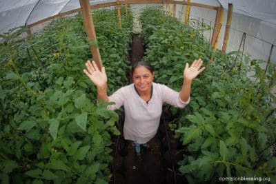 Berta raises her hands in praise and gratitude for the greenhouse opportunity that has changed her life.