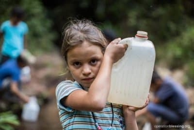 Maylee in Aldea Nueva carries a jug of unsafe water.