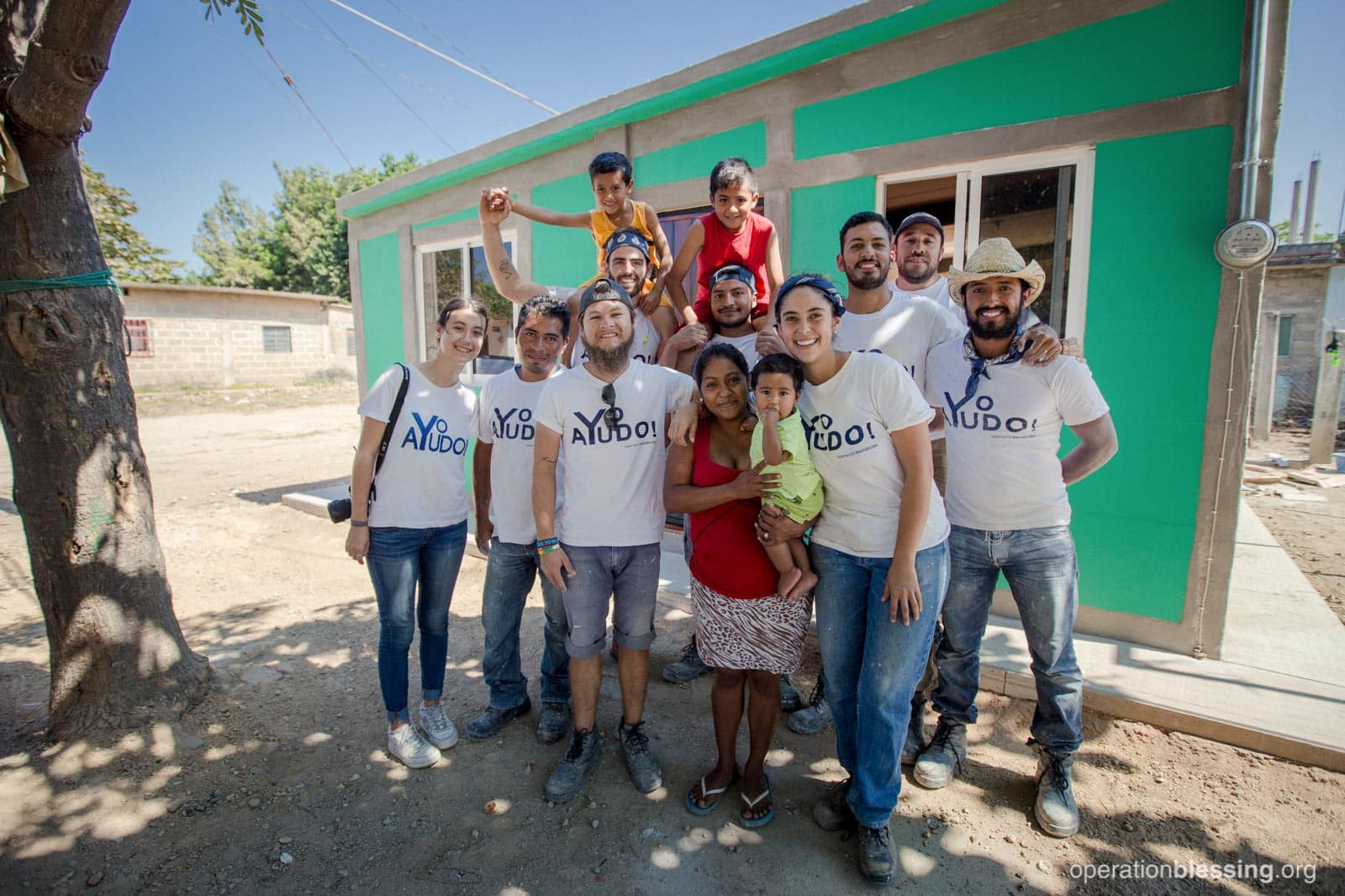 Luzbeth and her family pose with the Operation Blessing construction crew in front of their new home.