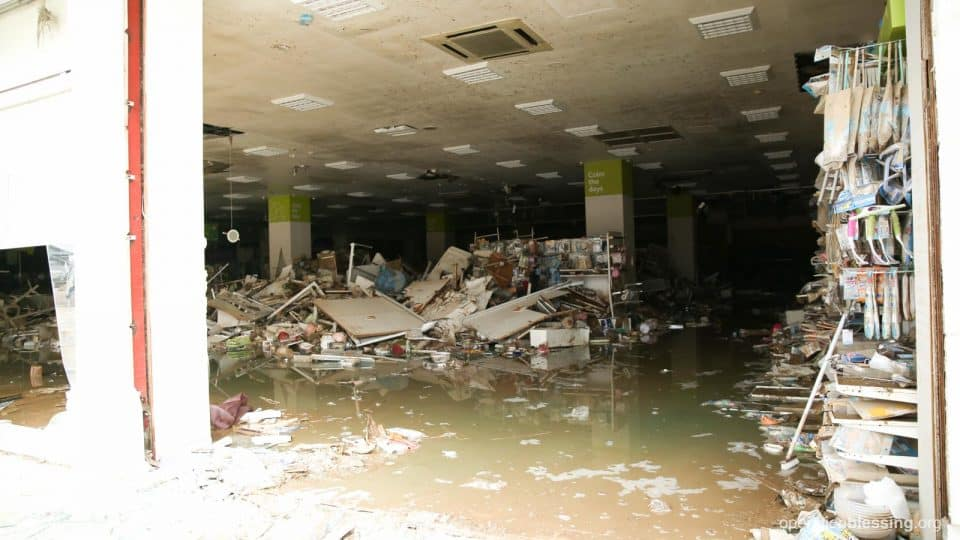 A flooded, mud-filled building in need of recovery.