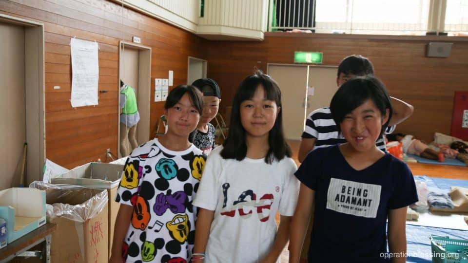 Kids in a shelter smile hopefully despite the recent tragedy in West Japan.