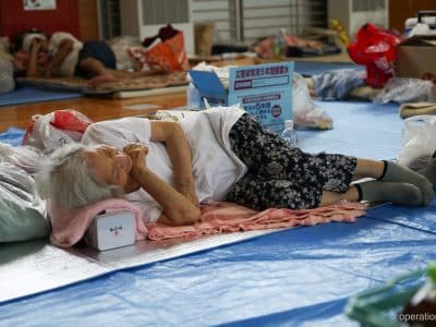 This elderly flood victim sleeps in a shelter in West Japan.