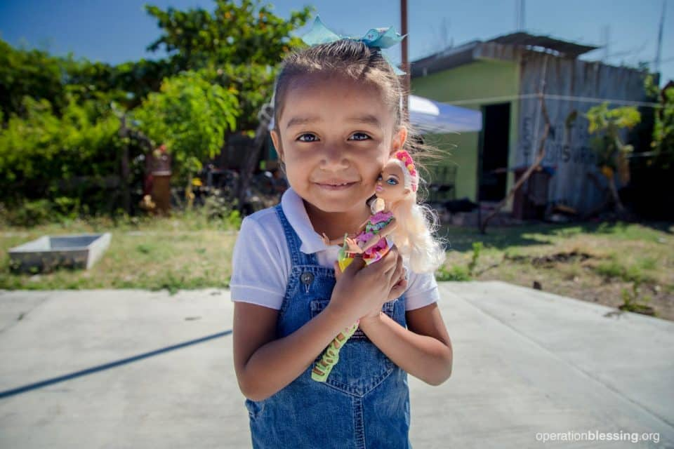 Allison, age 4, happily holding her new doll.