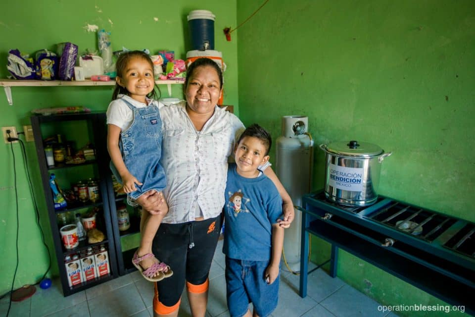 Roxana and her two children smile in front of their new kitchen that will revive their dessert business.