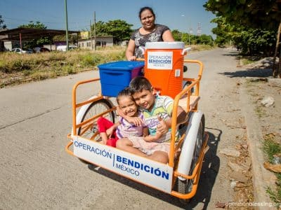 Roxana and her children with their new carrying cart for their dessert business from Operation Blessing.