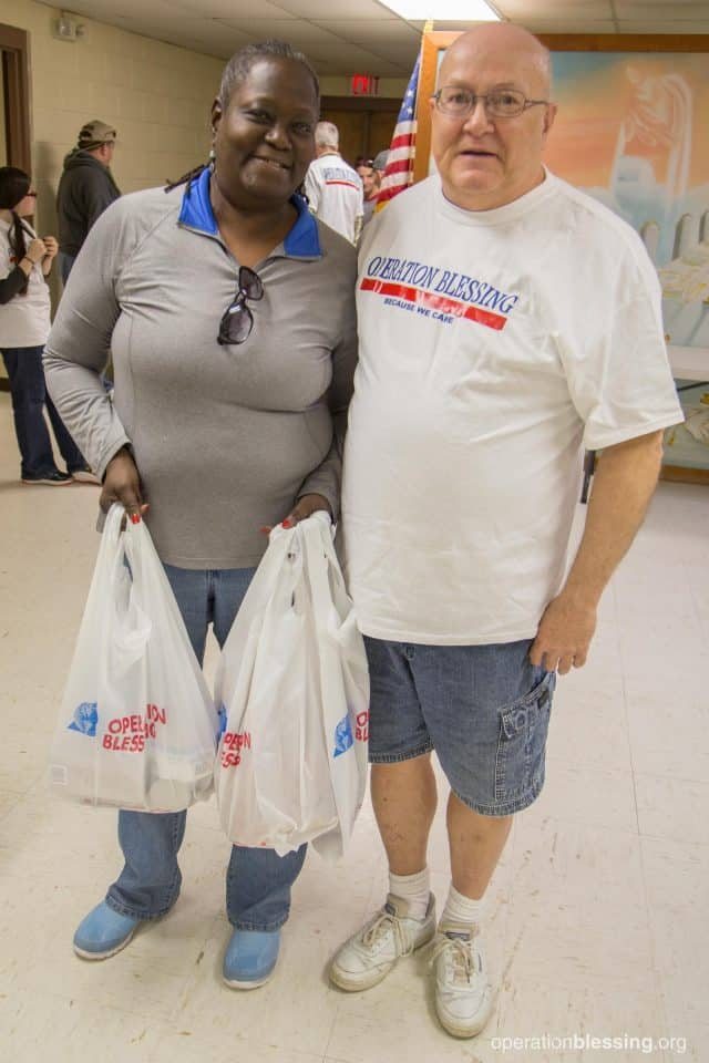 Cynthia gratefully accepts bags of groceries from a volunteer.