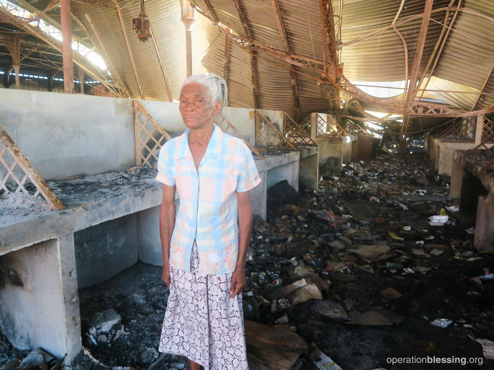 Guerrier stands among the ashes and ruin of the Iron Market fire in Haiti that destroyed her business.