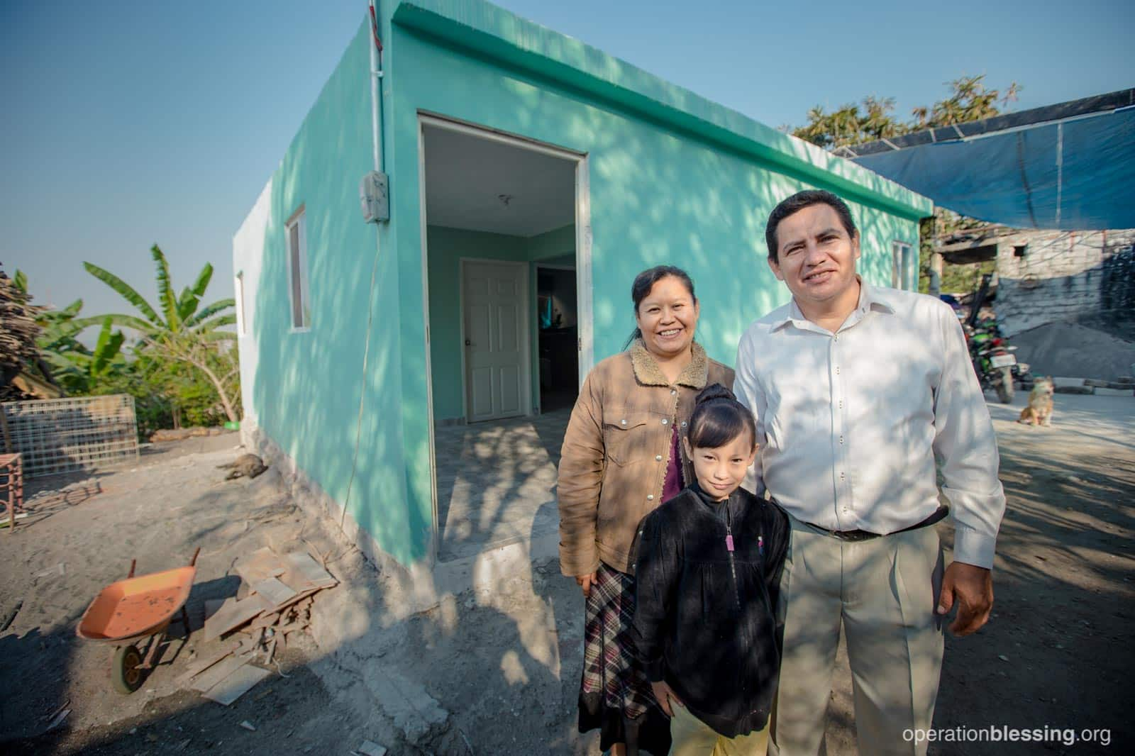 Pastor Rafael and his family smile as they stand in front of their newly rebuilt home.