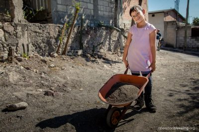 Pastor Rafael's daughter stands with a wheelbarrow as OBI rebuilds their home.
