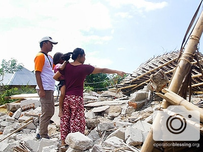 A woman points to her destroyed home in Indonesia as an Operation Blessing worker assesses the need for earthquake aid.