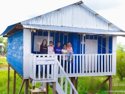 Moira and her family stand on the porch of their new home provided by Operation Blessing's home building project.