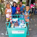 Ana Nuria and her children pose on her new cart provided by Operation Blessing for her small business.