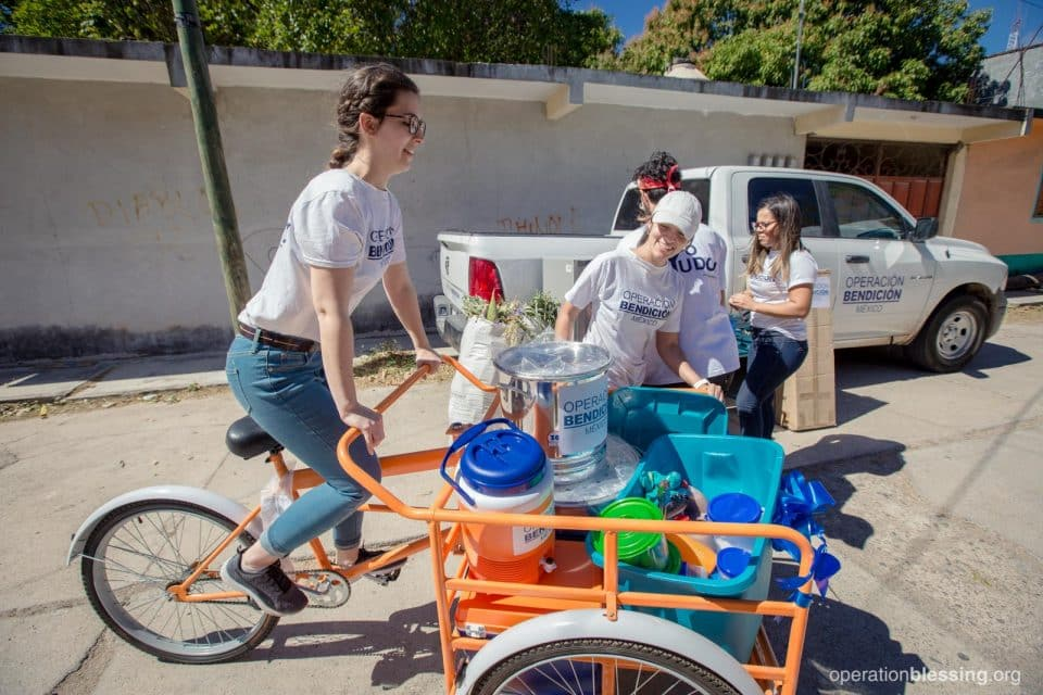 An OB Mexico team member rides the bike and supplies to Alexis and his family.