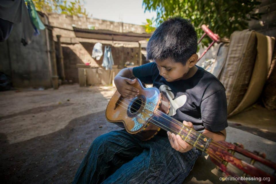 Alexis plays his father's guitar. A cooked corn business helped his abandoned family.