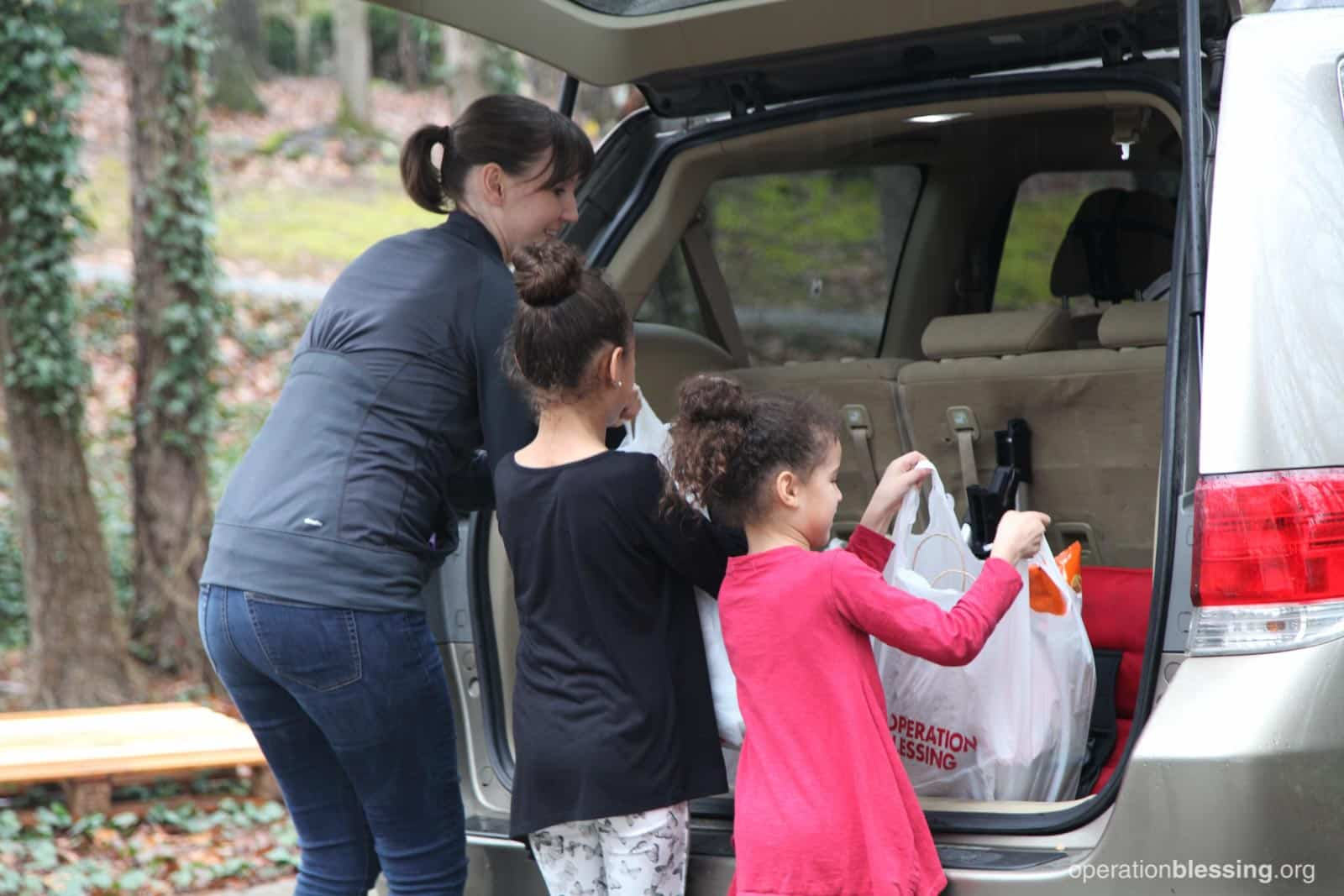 Lakashah and her daughters fill the trunk with free groceries.