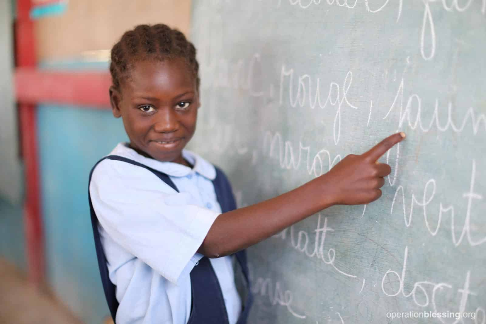 Daphkaline points at the chalkboard. This promising student received a scholarship to continue her education.
