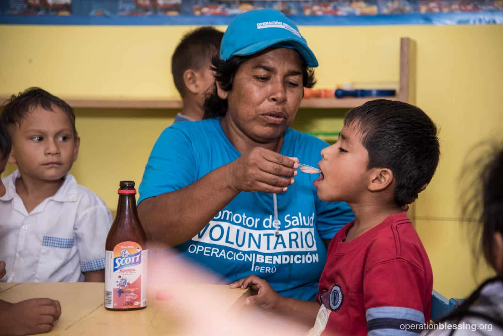 An Operation Blessing Community Health Worker gives a child nutritional supplements.