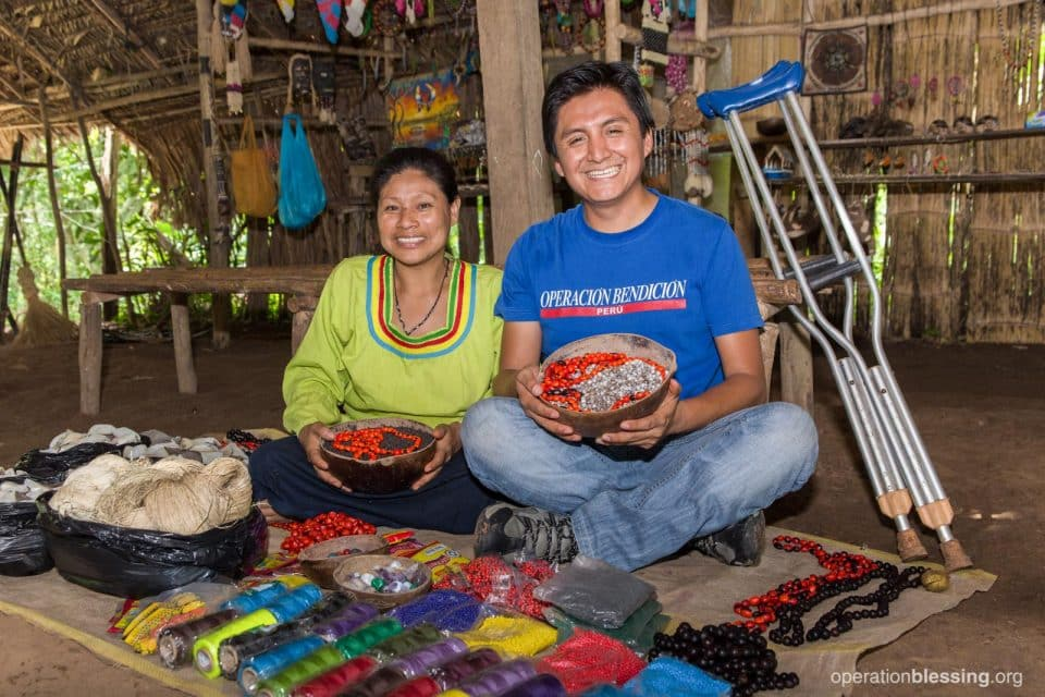 Loily sits with an Operation Blessing worker after receiving help with her handicrafts business.