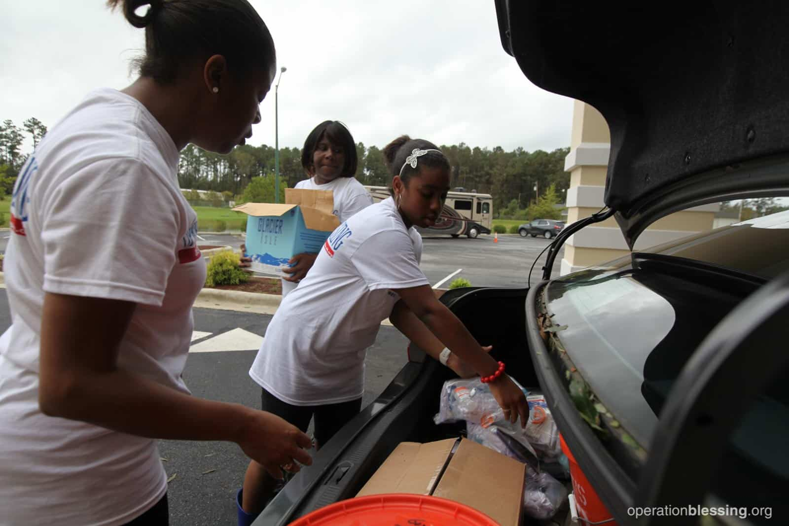 Volunteers loading cars with hurricane relief supplies.