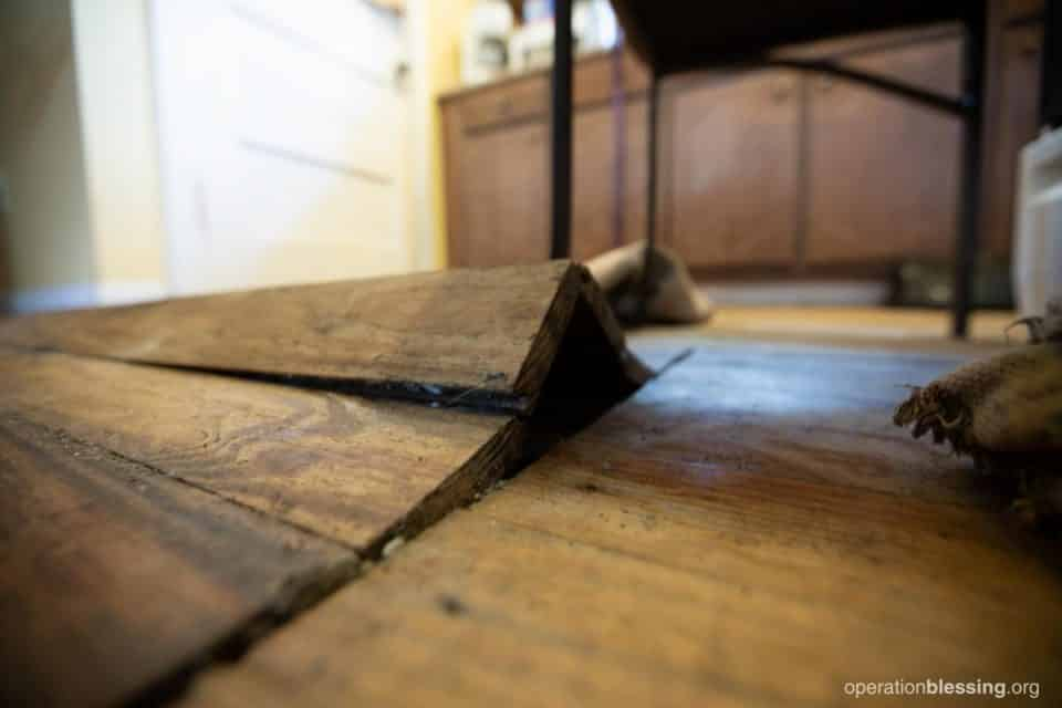 Buckled, water-damaged floors in John and Crystal's home.