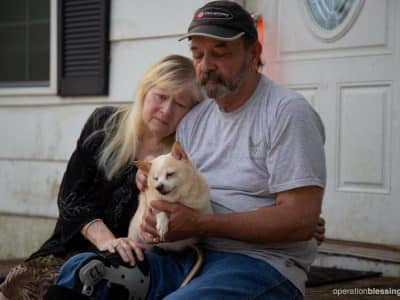 John, Crystal, and their dog sit on the porch of their flooded home. Miracles surround their escape from Hurricane Florence.