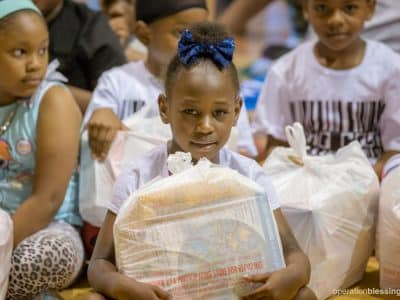 A young girl receives free groceries from Operation Blessing's Project Lunchbox.