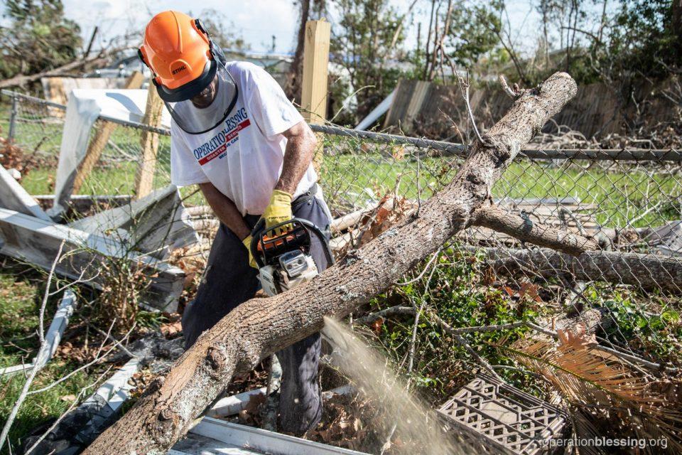 An OBI volunteer chopping fallen trees in Ed's yard.
