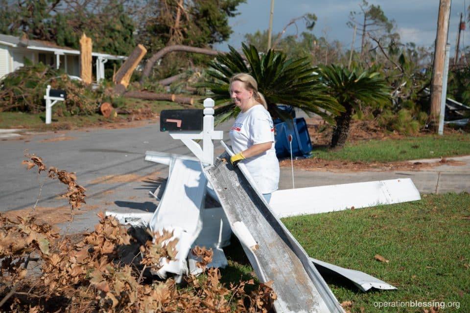 A female volunteer carries debris to the street.