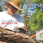 A volunteer chops fallen trees, reaching out to the victims of Hurricane Michael in Florida.