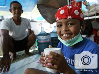 A victim of the Indonesia tsunami receives clean water and medical care.