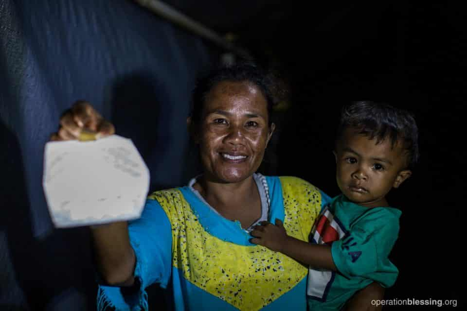 A mother holds a solar light provided by Operation Blessing.