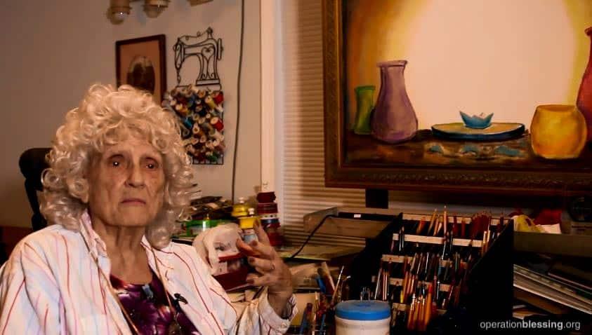 Marie shows the Broken Vessels painting in her art studio.