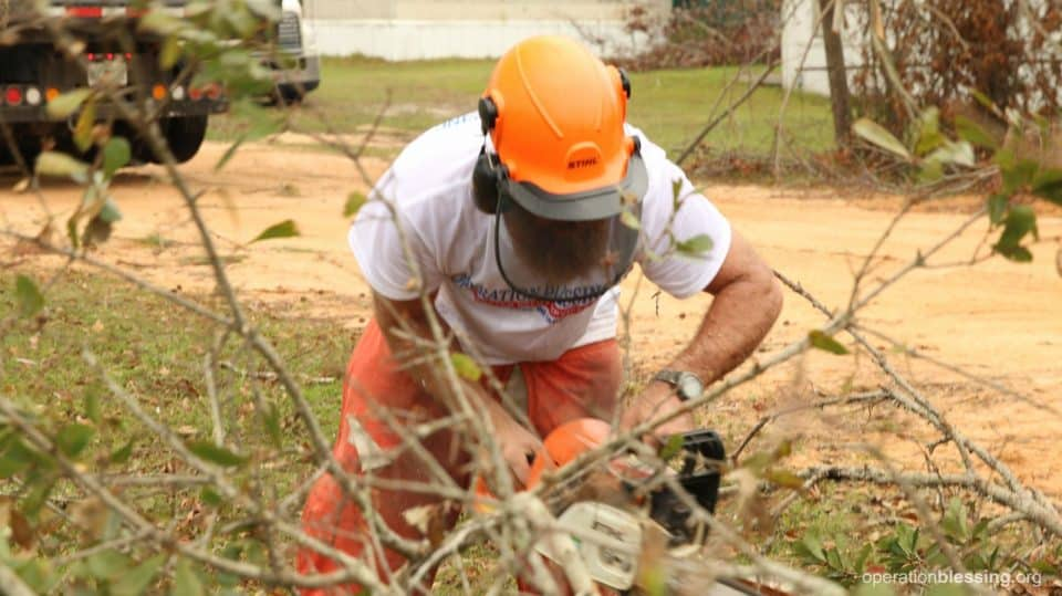 A volunteer using a chain saw on Gene and Marie's property.