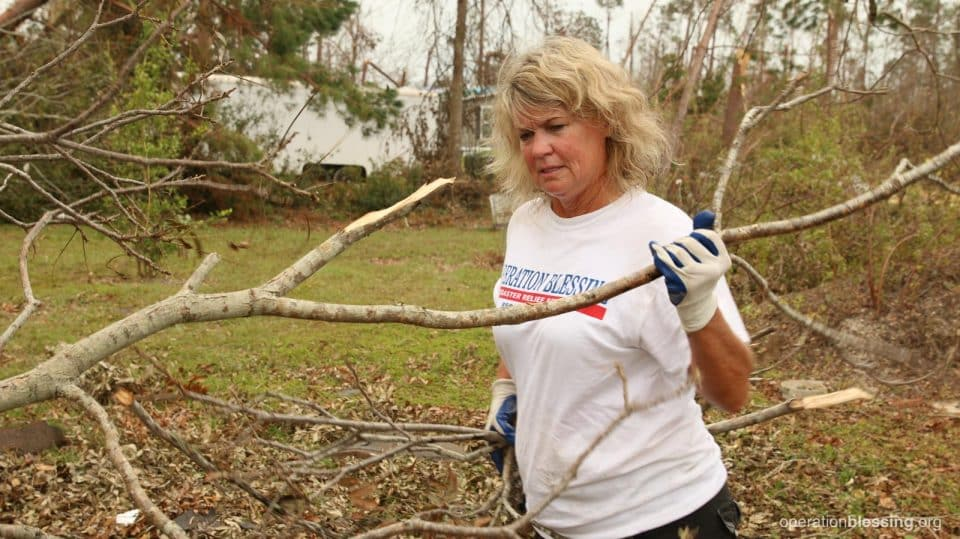 A female volunteer helps clear branches.