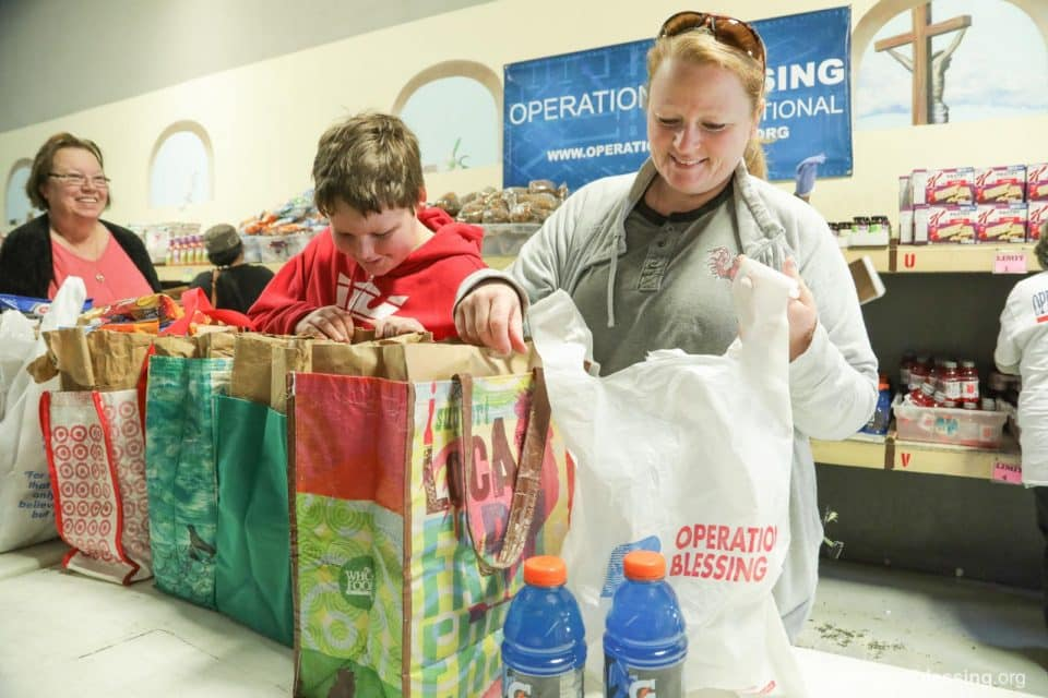 Jonathan and his mom pack free groceries after being helped through hard times by Operation Blessing and Warehouse of Hope.