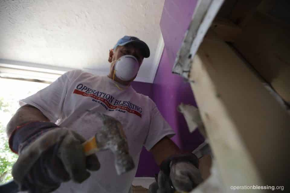 An Operation Blessing disaster relief volunteer helping with Divya's flooded home.