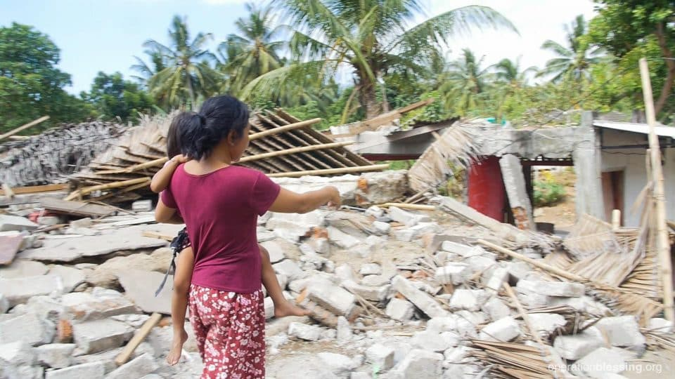 Putri's mother shows an Operation Blessing worker their destroyed home.