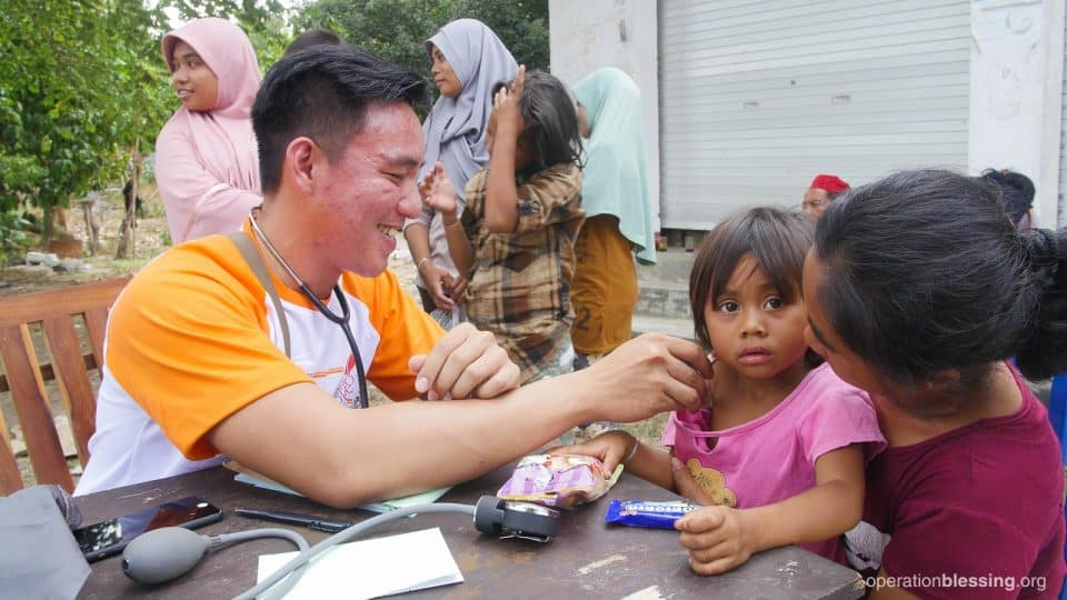 An Operation Blessing doctor attends to Putri.
