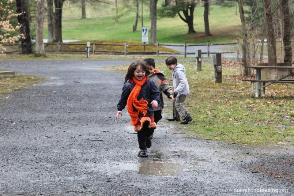 Three children rescued from bad circumstances happily play outside.