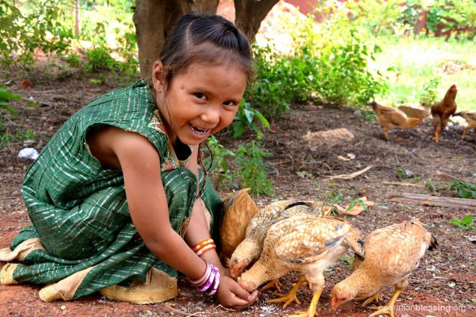 A happy, healthy Deepana playing with chickens.