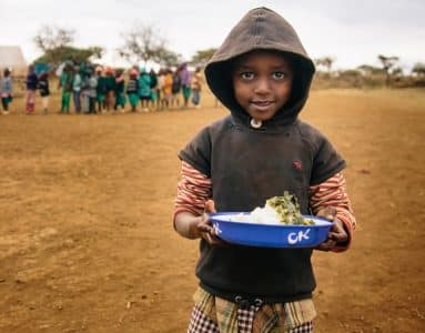 A young boy in Kenya holds a meal as part of Operation Blessing's four-fold approach to humanitarian relief.