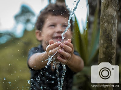 A young boy in La Estrella, Honduras relishes safe water provided by generous Operation Blessing.
